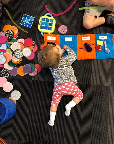 Image : Bébé allongé par terre qui lit un livre tactile des Doigts qui Rêvent