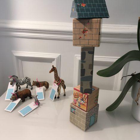 Animaux miniatures avec étiquette en braille à coté d'un empilement de cubes  en carton
