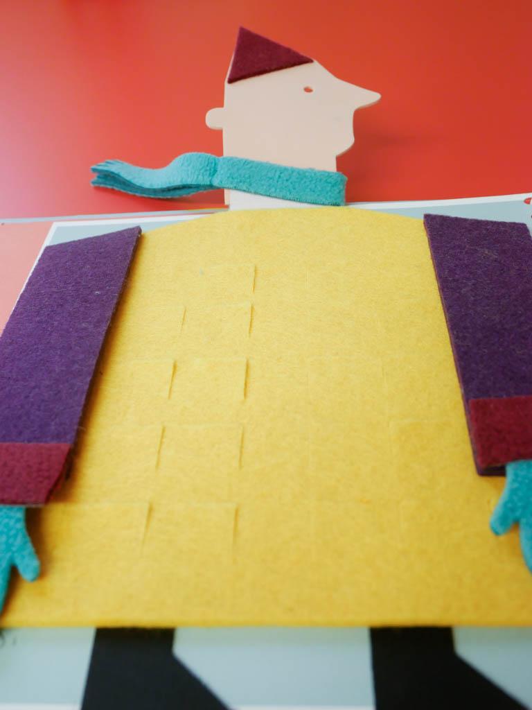 Le géant tactile avec un manteau en feutrine jaune plein de poches et des grands bras violets. Sa tête dépasse de la hauteur du livre afin qu'il soit présent à chaque page.