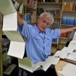 Photo de Philippe Claudet tenant un livre accordéon entre ses mains