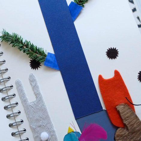 Photo d'une page du livre : on peut voir de dos l'écureuil orange ainsi qu'un lapin gris et un oiseau bleu cyan et à la queue mauve, tous les trois faits à partir de formes simples, plumes et fourrure. Ils regardent ensemble l'arbre du livre, un tronc en papier cartonné bleu avec des petites branches vertes de sapin artificiel.