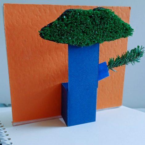 L'arbre du livre, déplié sur un fond orange à partir d'une page, est en papier rigide bleu. Il ressemble à un genre de baobab dont les feuilles au sommet sont faites de gazon artificiel.