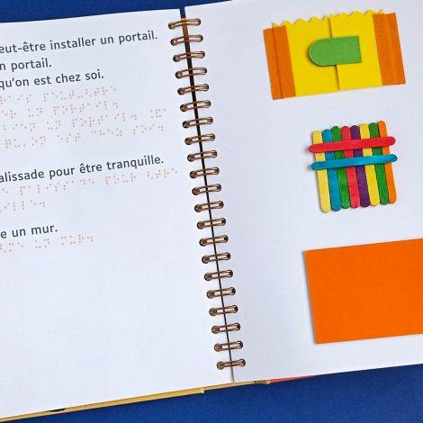 livre ouvert, texte bleu, braille orangé, illustrations portail, palissades, mur à plat