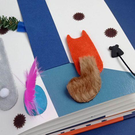 page d'illustrations avec lapin, oiseau, écureuil et souris vue de derrière, par leurs queues. Arbre avec ombre en vernis et branches manipulables, pommes de pins piquantes