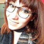 Photo de Jeanne Artous, une jeune femme souriante à lunettes et aux cheveux châtains.