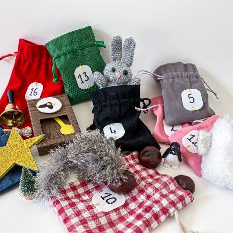 Photos des petits sac numérotés et de différentes couleurs qui servent de poches au manteau du géant. On retrouve parmi les objets et animaux éparpillés l'étoile, l'horloge, la souris, le lapin, la chouette, une petite cloche, des marrons…,